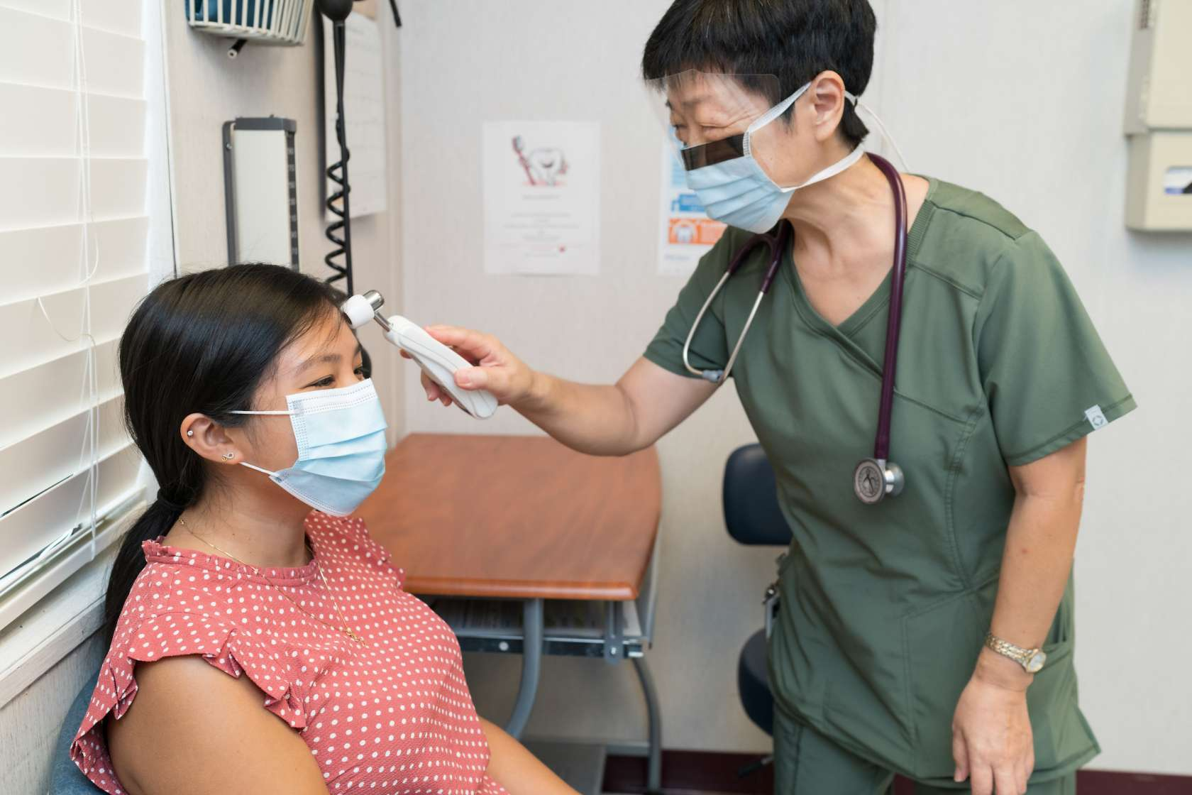 An female Asian nurse takes the temperature of a female patient.