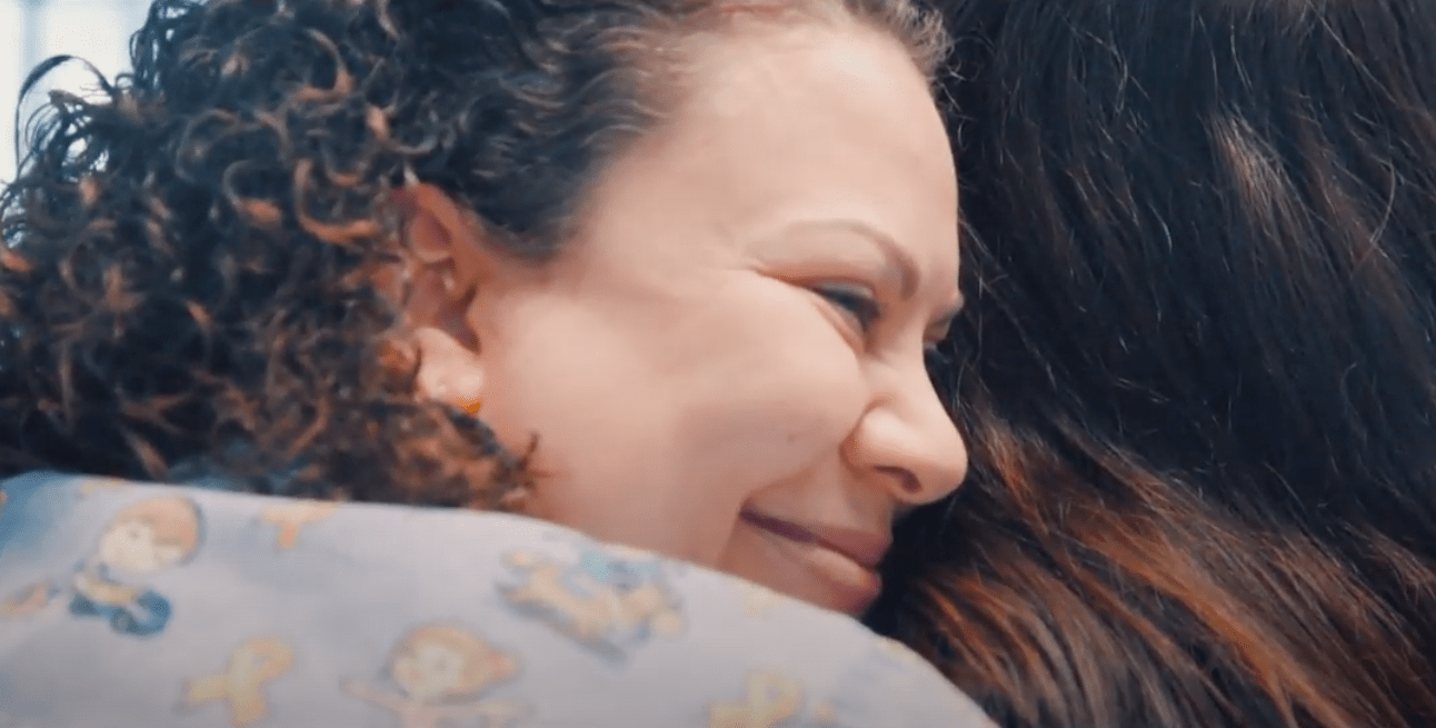 A woman hugs another woman.